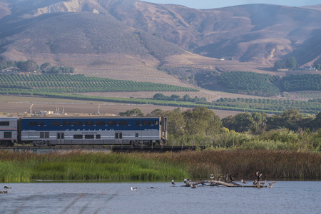 Surfliner Amtrak train speeding along the tracks traveling between estuary pond and agriculture mountains on July 14, 2018 in Ventura, California.