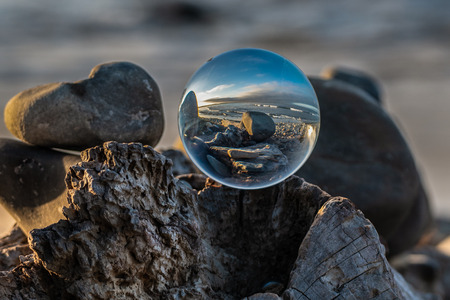 Spherical lens sitting atop driftwood log under the morning light of dawn along this California beach scene.