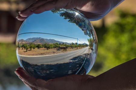 Lonely country road through rural California seen through round ball lens with Ojai mountains behind tree orchard. Stock Photo
