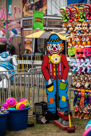 Clown figured decorating High Striker mallet and bell game of the county fair entices players with plush prizes on display.