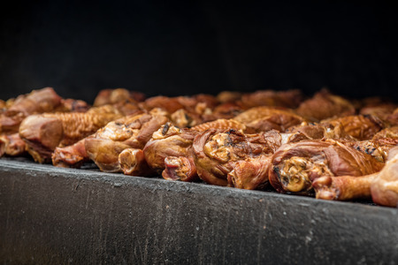 Smoked bareque chicken cooking on the BBQ grill over flavoring wood logs at county fair. Stock Photo