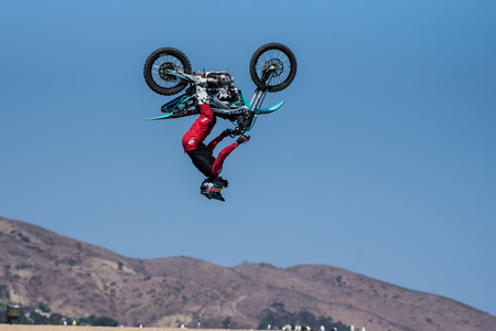 Stunt rider in red costume upside down during apex of backflip on jump during Flying U Rodeo at Ventura County Fair on August 12, 2018 in California.