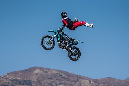 Stunt rider in red costume skitches to side on jump during Flying U Rodeo at Ventura County Fair on August 12, 2018 in California.