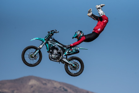 Stunt rider in red costume hangs on to seat of motorcycle while flying across the sky on jump during Flying U Rodeo at Ventura County Fair on August 12, 2018 in California.