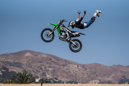 Stunt rider in black costume flies in midair over bike with arms spread on jump during Flying U Rodeo at Ventura County Fair on August 12, 2018 in California.