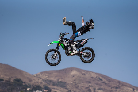 Stunt rider in black costume lifting leg in air with arms spread wide on jump during Flying U Rodeo at Ventura County Fair on August 12, 2018 in California. Publikacyjne