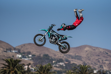 Stunt rider in red costume freefalls in midair over bike with arms spread on jump during Flying U Rodeo at Ventura County Fair on August 12, 2018 in California.