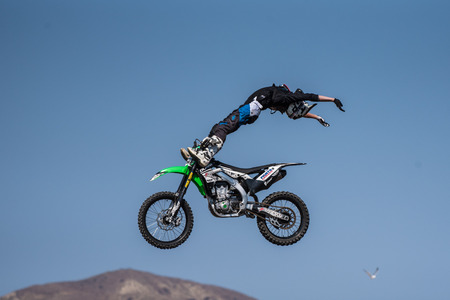 Stunt rider in black costume performing christ pose with toes under handlebars on jump during Flying U Rodeo at Ventura County Fair on August 12, 2018 in California.