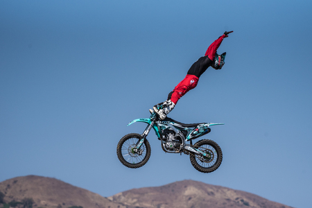 Stunt rider in red costume performing christ pose with toes under handlebars on jump during Flying U Rodeo at Ventura County Fair on August 12, 2018 in California.