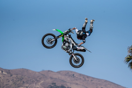 Stunt rider in black costume hangs on to bike with feet off to side of motorcycle on jump during Flying U Rodeo at Ventura County Fair on August 12, 2018 in California.