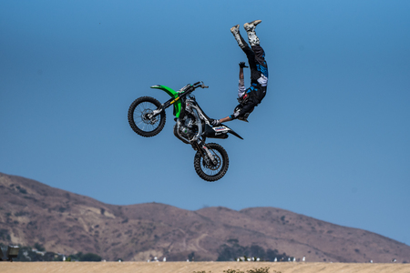 Stunt rider in black costume performs tail grab handstand on jump during Flying U Rodeo at Ventura County Fair on August 12, 2018 in California. Editorial