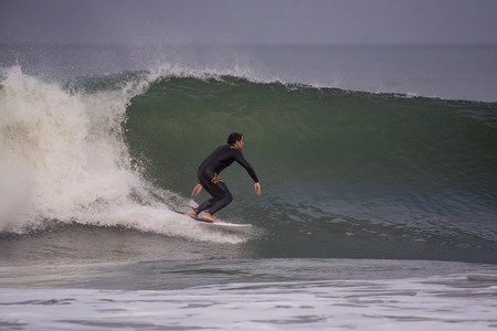 Surfer gaining speed down the line on wave pushed into Ventura by Hurricane Lane at Surfers Knoll Beach in California on August 17, 2018. Editorial