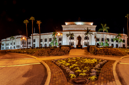 Panoramic view of Ventura City Hall building lit up at night with landscaping and Junipero Serra statue in front on August 17, 2018 in California, USA.