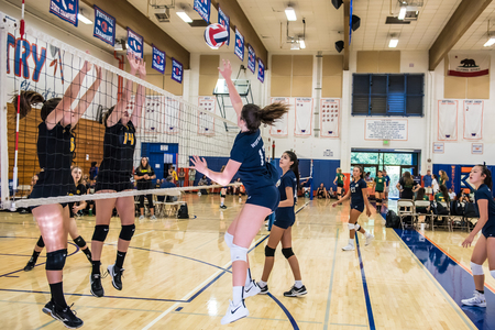 Middle blocker for West Ranch High Schools freshman-sophomore volleyball team uses finese to push ball past defense of Newbury Park during the Westlake, California tournament played on August, 25, 2018. Editorial