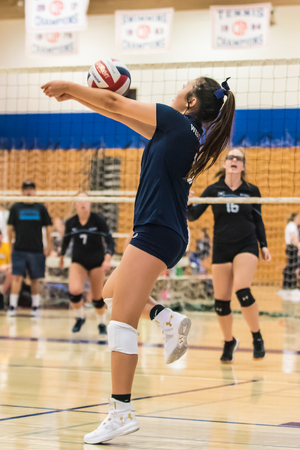West Ranch High School volleyball pleyer from the freshman-sophomore team concentrates as she bumps a pass during game of Westlake, California tournament played on August, 25, 2018.