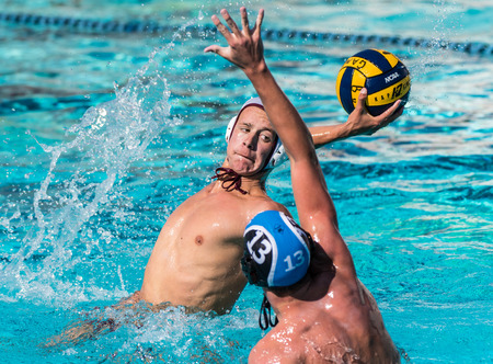 Foothill Technology High Schools player elevates out of water to create opening for shot on goal and Buenas defender attempts to block during game played in Ventura, California on August 28, 2018. Editorial