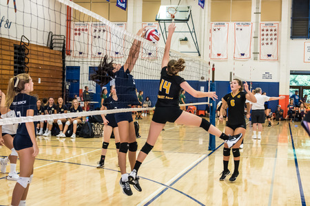 Middle blocker for Newbury Park High Schools freshman-sophomore volleyball team times her jump perfectly to block hit of West Ranch during the Westlake, California tournament played on August, 25, 2018.