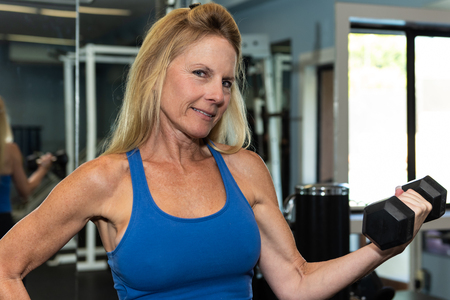 Female middle age fitness model shows muscular and lean arm strength while performing a dumbbell curl in gym.