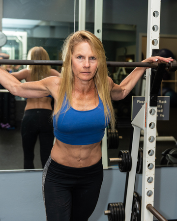 Serious female weight lifted showing strong abdominal muscles while posed in gym squat rack.