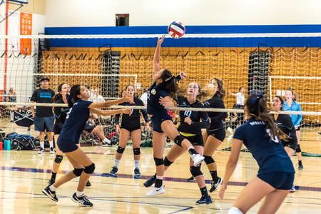 Middle blocker for West Ranch High Schools freshman-sophomore volleyball team uses her finger tips to push ball over net as Buenas defense reacts during the Westlake, California tournament played on August, 25, 2018.