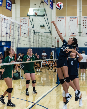 Middle blocker for West Ranch High Schools freshman-sophomore volleyball team times her jump to hit ball high in the air as defense of Moorpark looks on during the Westlake, California tournament played on August, 25, 2018. Editorial