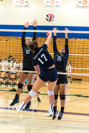 Middle blocker for West Ranch High Schools freshman-sophomore volleyball team times her jump to hit ball between the Buena defenders during the Westlake, California tournament played on August, 25, 2018. Editorial