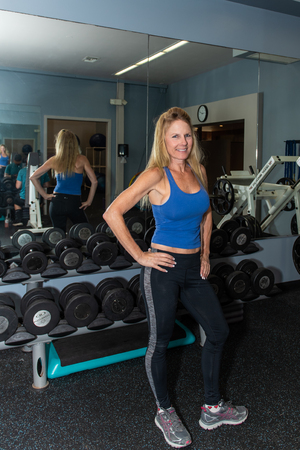 Healthy middle age female content with life and ready to exericse in free weight room.