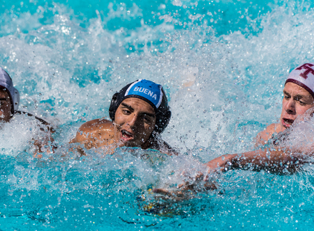 Water Polo players from Buena and Foothill Technology High Schools race for submerged ball in a white water frenzy during match played in Ventura, California on August 28, 2018.