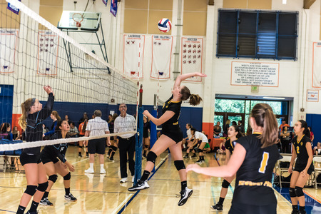 Outside hitter for Newbury Parks freshmansophomore high school volleyball team is up in the air ready to strike the ball during Westlake, California tournament played on August 25, 2018.  Defense players of Buena High School look on.