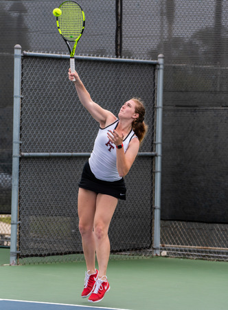 High school varsity tennis player from Foothill Tech focused on hitting a serve during her match against St Bonaventure on September 4, 2018. Editorial