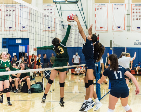 Middle blockers for West Ranch and Moorpark High Schools freshman-sophomore volleyball team have hands on ball over net simultaneously during the Westlake, California tournament played on August, 25, 2018.