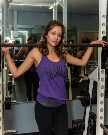 Latina fitness trainer looking casual and cool with arms resting on squat bar. Foto de archivo - 112041340