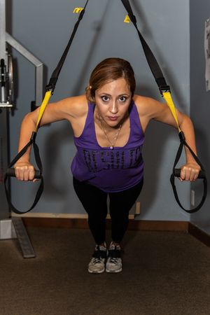 Young Latina fitness trainer demonstrating perfect form on suspended push up exercise in gym.