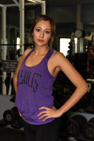 Young and attractive Latina woman posed with confidence and hands on hips in workout room.