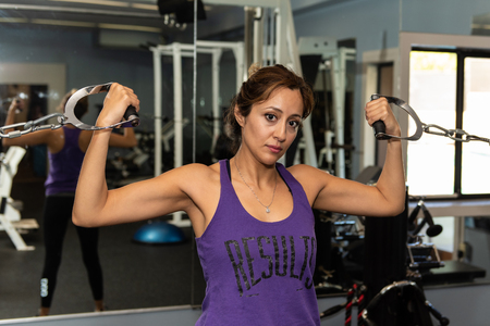 Young Latina fitness trainer holding double bicep pose using cable crossover machine in gym. Stock Photo