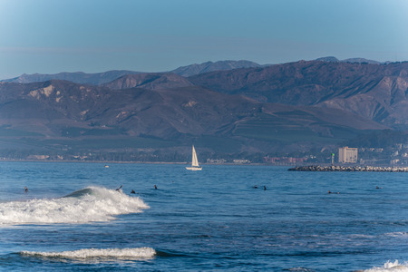 Small craft sail boat navigating past surfers in into the open ocean on a sunny weekend of September 30, 2018 in California. Stock Photo