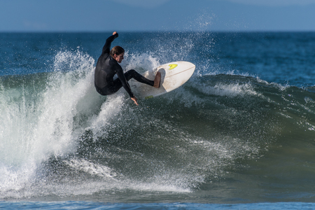 Surfer in black wetsuit glides along the pitching lip of a wave at Surfers Knoll, Ventura, California on October 1, 2018.