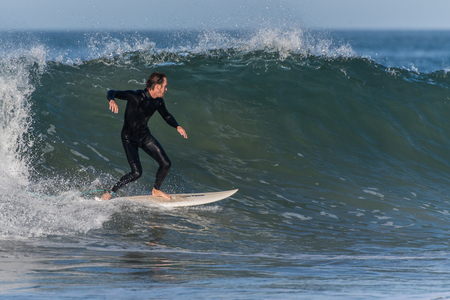 Surfer in black wetsuit finds smooth and glassy section of wave at Surfers Knoll, Ventura, California on October 1, 2018.