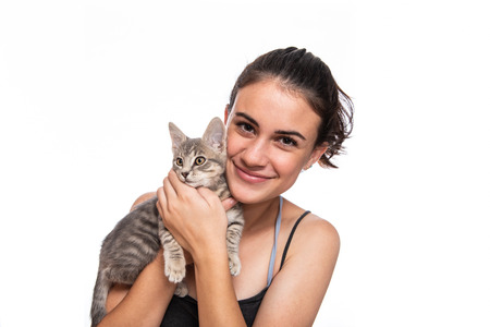 Teenage girl snuggling faces with her furry and cute grey tabby kitten.