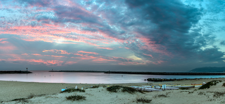 Panoramic scene of golden hour clouds over smooth water of Ventura Harbor Cove under Autumn dusk sky.