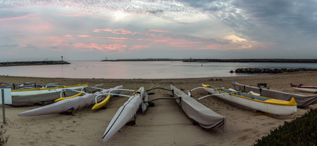Panoramic scene of golden hour clouds over outrigger rower boats of Ventura Harbor Cove under Autumn dusk sky.