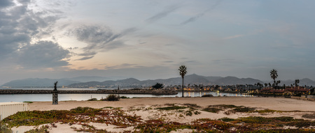 Panoramic scene of golden hour clouds over matching mermaid statues of Ventura Harbor mouth under Autumn dusk sky.