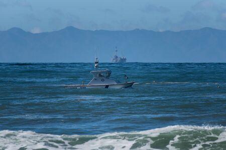 Ventura Harbor Patrol boat cruising across Marina Park with oil platform and Santa Cruz Island in the background on November 23, 2018 in California, USA. Editöryel