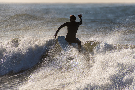 Silhouette of surfer riding up to the lip of a breaking wave in cold Pacific Ocean in Southern California.