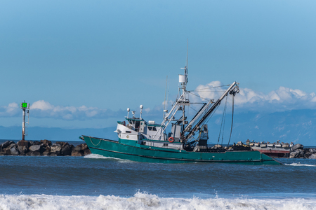 Commercial fishing boat heading out the safety of the harbor and out into the open ocean.
