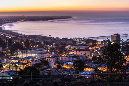 Downtown Ventura, California, USA in panoramic view, is nestled against the Pacific Ocean coastline as building lights glow on the streets during winter on December 23, 2018. Standard-Bild