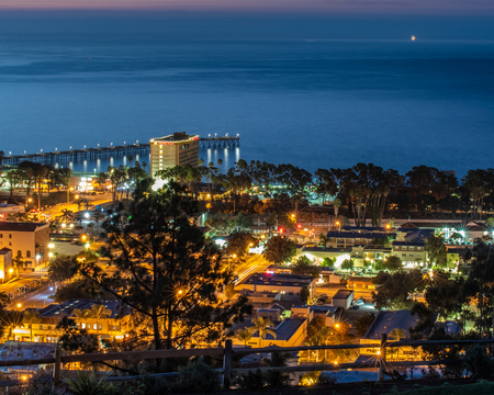 Downtown Ventura, California, USA is nestled against the Pacific Ocean coastline and lit up in the predawn hours of winter on December 23, 2018.