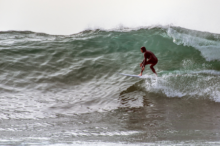 Regular foot surfer in wearing hood, dropping in going right on large waves from winter swell in Santa Barbara, California, USA on January 9, 2019. Stock Photo