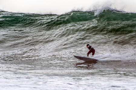 Regular foot surfer in wearing hood, looking up during bottom turn going right on large waves from winter swell in Santa Barbara, California, USA on January 9, 2019.