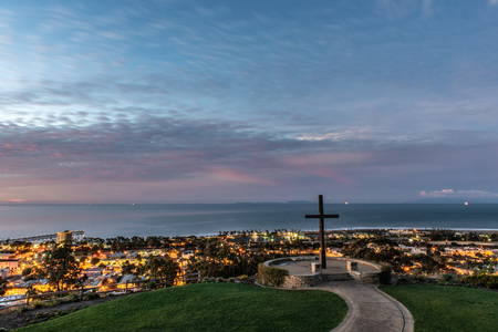 Christian wooden cross stants tall over city lights of Ventura along the Pacific Ocean coast as dawn begins to light the cloudy sky.